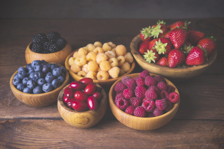 Blackberry, strawberry, yellow and red raspberries, dogwood in wooden bowls on a dark wooden old background in vintage style.